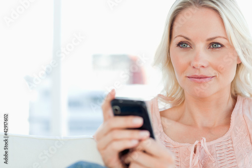 Close-up of a blonde with a mobile on a sofa
