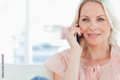 Close-up of a blonde phoning on a divan