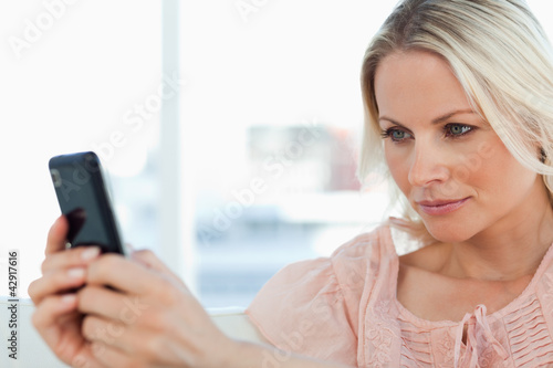 Close-up of a blonde texting on a sofa