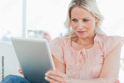 Surprised blonde using a touchpad