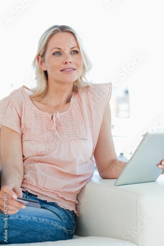 Thoughtful blonde buying online with a touchpad