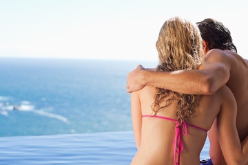 Back view of couple sitting on the pool edge