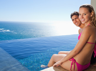 Smiling couple sitting on the pool edge