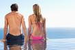 Back view of couple sitting on the pool edge looking at the sea