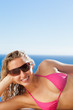 Smiling woman with sunglasses sunbathing on the pool edge