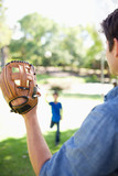 Father uses the baseball glove to catch the ball