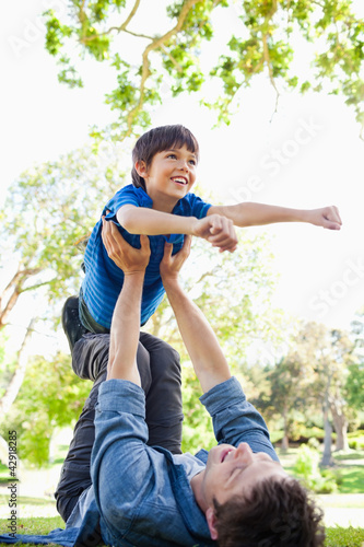 A boy with his arms out smiling as his dad holds him up