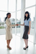Two serious businesswomen shaking hands while looking at camera