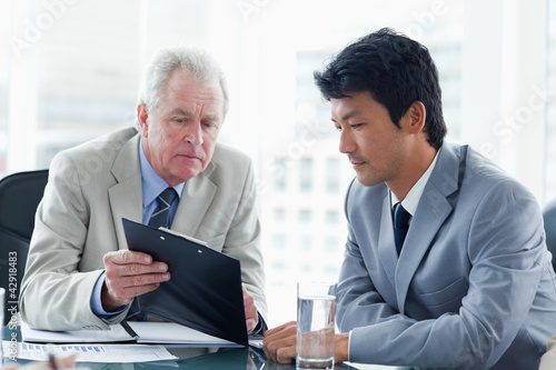 Serious businessman showing a clipboard to an employee