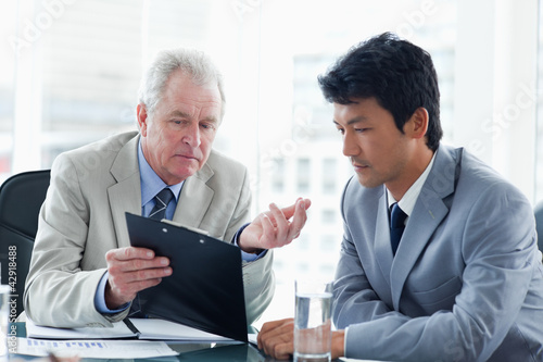 Mature businessman giving serious explanations about information on the clipboard to an employee