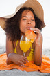 Young relaxed woman closing her eyes while lying on the beach with a cocktail