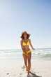 Young smiling woman wearing a straw hat while standing on the beach