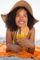 Young smiling woman in beachwear lying on the beach while drinking a cocktail