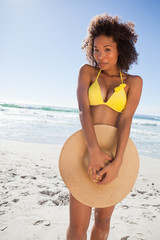 Young happy woman hiding her bikini with her straw hat