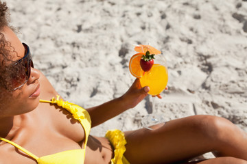 Young attractive woman sitting on the beach with a fruit cocktail