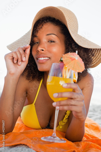 Young attractive woman holding her hat brim while lying down with a cocktail