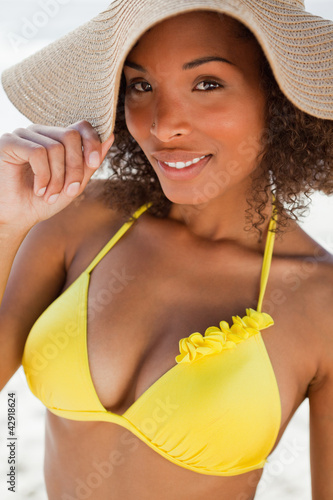 Young attractive woman standing on the beach while holding her hat brim