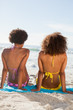 Rear view of young attractive women sitting on beach towels