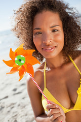 Young attractive woman looking at the camera while holding a pinwheel