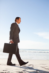 Young businessman walking on the beach