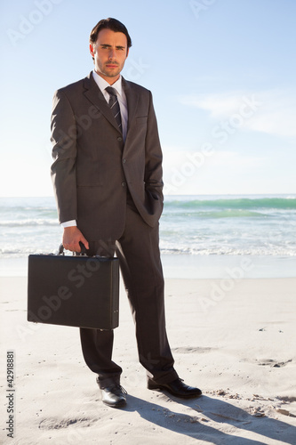 Businessman standing upright on the beach