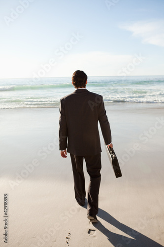 Rear view of a serious businessman walking on the beach
