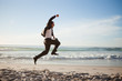 Successful businessman jumping on the beach