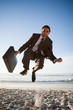 Successful businessman showing his happiness by jumping on the beach