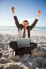 Happy businessman raising his arms in success while sitting on the beach
