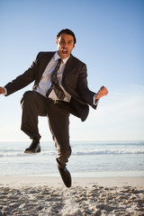 Young businessman shouting while jumping on the beach