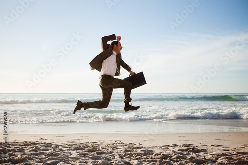 Young businessman jumping on the beach with his briefcase