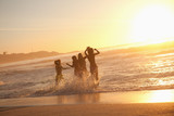 Young happy women dancing in the water at sunset