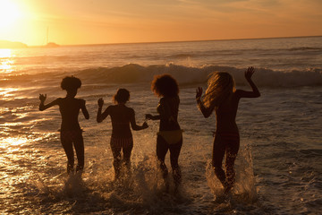 Four young women walking in the water together