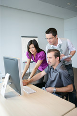 Dynamic trio working at a desktop computer
