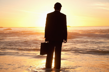 Young businessman looking at the ocean