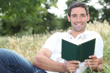 Smiling man reading a book in a field