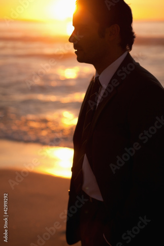 Young businessman standing on the beach at sunset