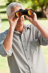 Old man looking through a binoculars