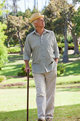 Old man with hat and walking stick in park looking up