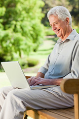 Old man is sitting down with his laptop and smiling