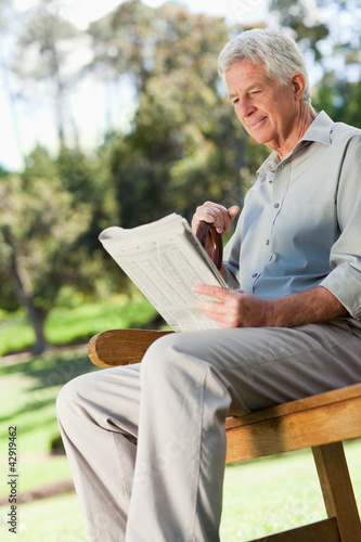 Old man sitting down smiling and holding a newspaper