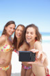 Three women in bikinis pose for a photo