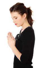 Young beautiful woman is praying.