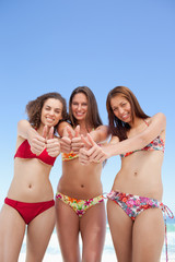 Three women looking downwards while putting their thumbs up