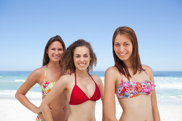 Three friends looking to the side while smiling in bikinis