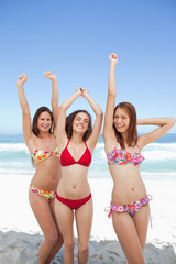 Three friends happily raising their arms on a beach