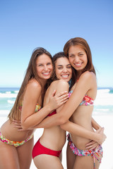 Three friends hugging each other while smiling