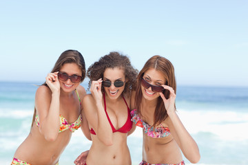 Three friends looking over their sunglasses on the beach