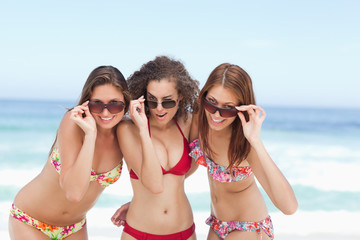 Three women smiling happily while looking over their sunglasses