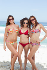 Three friends with their arms around each other as they stand on the beach